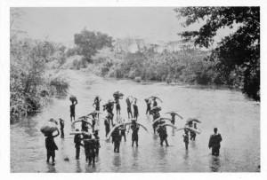 An ivory hunter's caravan fords a stream