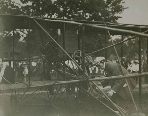 Hamilton making adjustments to his biplane, 1911