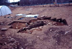 The Daniels house in Waterford during excavation, showing the stone-lined cellar hole that had been buried in a field. Beyond the cellar is a highway entrance ramp that was built over a colonial-era road. The white tent in the background had been placed over the cellar so it could be excavated in the winter. - AHS, Inc., Storrs