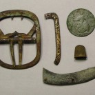 Various personal items from the Goodsell site: a plain brass shoe buckle, a fragment of a silver shoe buckle frame with a repair, a 1746 George II halfpenny, a child's small thimble, and part of a brass jackknife handle with a rococo design - AHS, Inc., Storrs