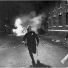 During the city riots of July 1967, a Hartford policeman dashes up Kennedy Street toward Main Street as tear gas spreads behind him. Hartford exploded that month when black residents in North Hartford rioted against continuing discrimination, poor housing, their treatment at the hands of police, and the lack of job opportunities. Photograph by Ellery G. Kington - Hartford Times Collection, Hartford History Center, Hartford Public Library