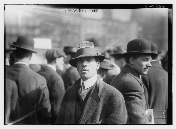"Man wearing a hat with card stating ""Bread or Revolution"""