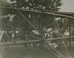 Hamilton making adjustments to his biplane, 1911